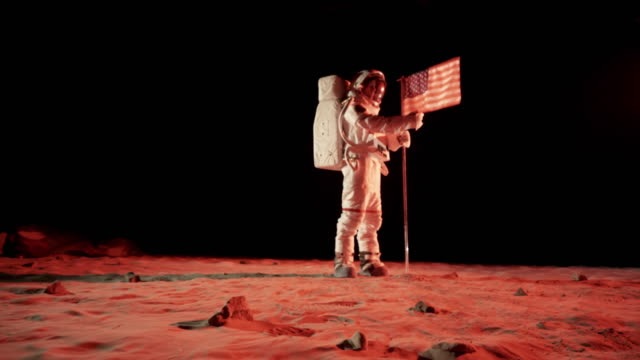 WS ZI SLO MO Astronaut putting up American flag on Mars and saluting / Berlin, Germany