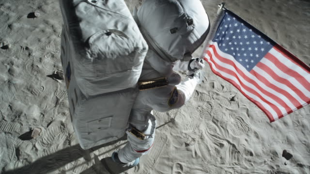 vídeos de stock e filmes b-roll de ms slo mo astronaut putting up american flag on moon and saluting / berlin, germany - lua