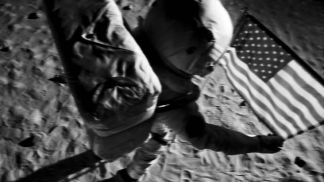 vídeos de stock e filmes b-roll de ms slo mo b/w astronaut putting up american flag on moon and saluting / berlin, germany - monocromo