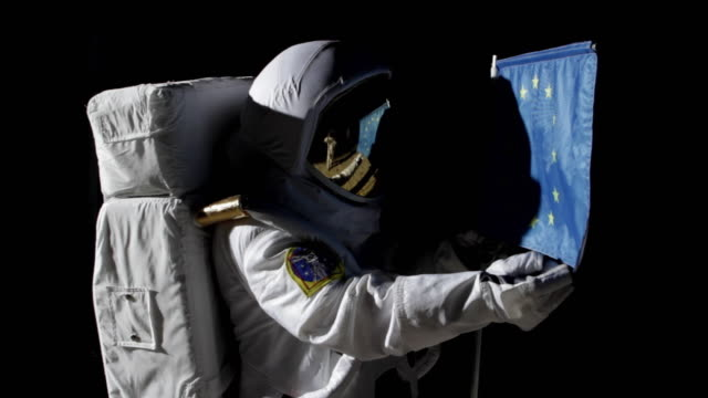 CU ZI Astronaut putting up European Union flag on moon and saluting  / Berlin, Germany
