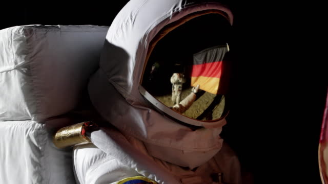 cu zi astronaut putting up german flag on moon and saluting / berlin, germany - helm stock-videos und b-roll-filmmaterial
