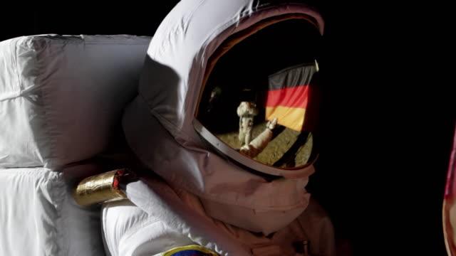 CU ZI Astronaut putting up German flag on moon and saluting / Berlin, Germany