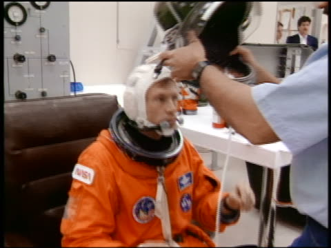 Astronaut Richard Searfoss sitting in spacesuit as man helps him put on helmet / STS76