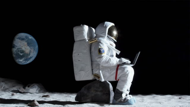 ws slo mo astronaut sitting on rock on the moon using laptop / berlin, germany - astronaut stock videos & royalty-free footage