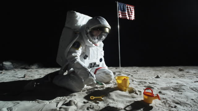 ws zo slo mo astronaut sitting on the moon's surface playing with sand pail and shovel / berlin, germany - out of context stock videos & royalty-free footage
