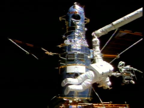 astronaut steven smith doing repairs on hubble space telescope during eva / sts82 - sternenteleskop stock-videos und b-roll-filmmaterial