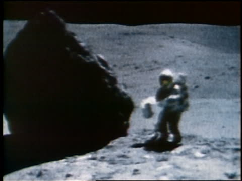 vídeos y material grabado en eventos de stock de astronaut taking soil sample by large boulder then bouncing away on moon / apollo 16 - boulder rock