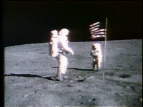 astronaut turning + saluting by american flag as other astronaut takes photograph on moon - saluting stock videos & royalty-free footage