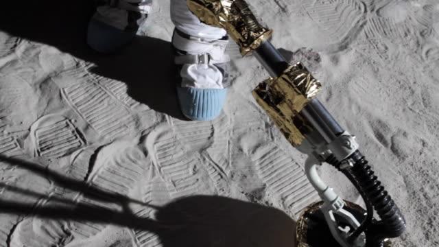 vídeos de stock e filmes b-roll de cu astronaut using metal detector on the moon / berlin, germany - pegada
