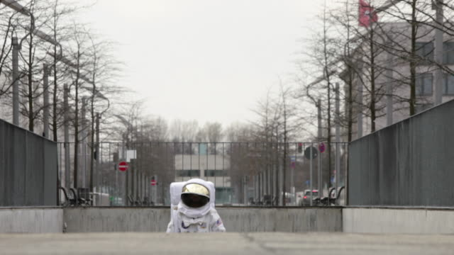 ws r/f astronaut walking up sidewalk in city / berlin, germany - astronaut stock videos & royalty-free footage