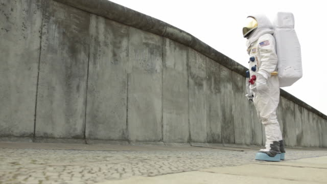 ws astronaut walking up to surrounding wall in city and then walking away / berlin, germany - astronaut stock videos & royalty-free footage