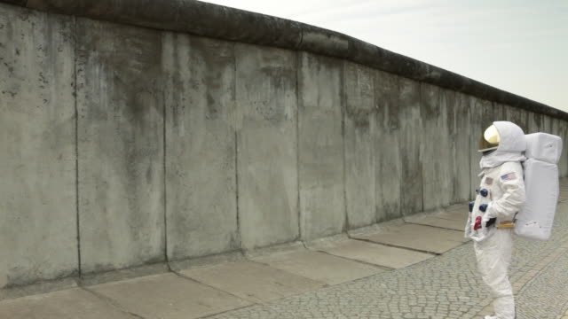 WS Astronaut walking up to surrounding wall in city, knocking on it and then walking away / Berlin, Germany