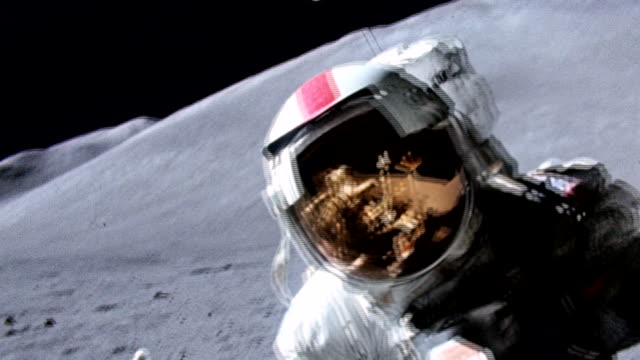 astronaut wearing new a7lb spacesuit on moon surface during apollo 15 mission / reflection seen in visor of spacesuit / astronaut collecting samples... - apollo 15 stock-videos und b-roll-filmmaterial