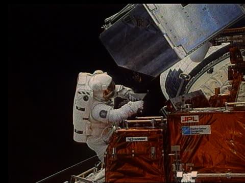 astronaut with metal box in open shuttle bay - 宇宙服点の映像素材/bロール