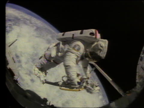 astronaut working in space with earth in background - astronaut stock videos & royalty-free footage