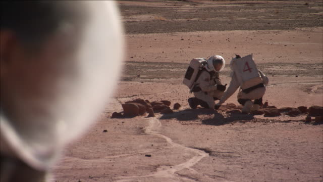 astronauts examine rocks in a desert. - space exploration stock videos & royalty-free footage