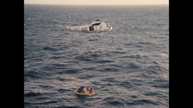 vídeos de stock e filmes b-roll de astronauts from the apollo 11 mission are airlifted via helicopter after landing in the ocean to the uss hornet, having completed the first manned... - prt