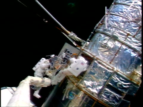 astronauts harbaugh tanner doing repairs on hubble space telescope during eva / sts82 - sternenteleskop stock-videos und b-roll-filmmaterial