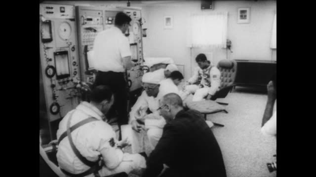 astronauts michael collins and john young walk in front of nasa group shaking hands with crowd behind barricade / climb into car and drive away / in... - 宇宙服点の映像素材/bロール