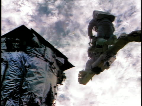 astronauts on robotic arm near hubble space telescope during eva / earth in background / sts82 - sternenteleskop stock-videos und b-roll-filmmaterial