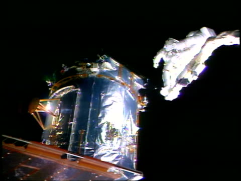astronauts on robotic arm near hubble space telescope during eva / sts82 - sternenteleskop stock-videos und b-roll-filmmaterial