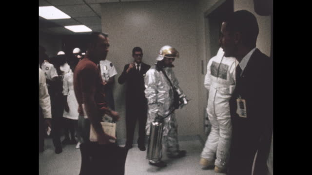 vídeos de stock e filmes b-roll de astronauts walk down the hallway and wave towards staff as they head to the elevator for the apollo-11 launch, the first manned space craft due to... - prt