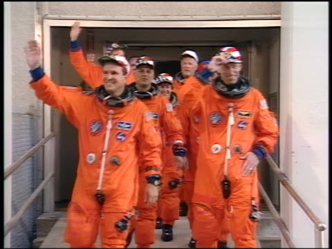 PAN astronauts waving as they walk towards bus before shuttle launch / STS86