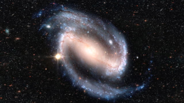 Astrophysics.  Animation of a Cepheid variable star varying in brightness in the arm of a spiral galaxy.