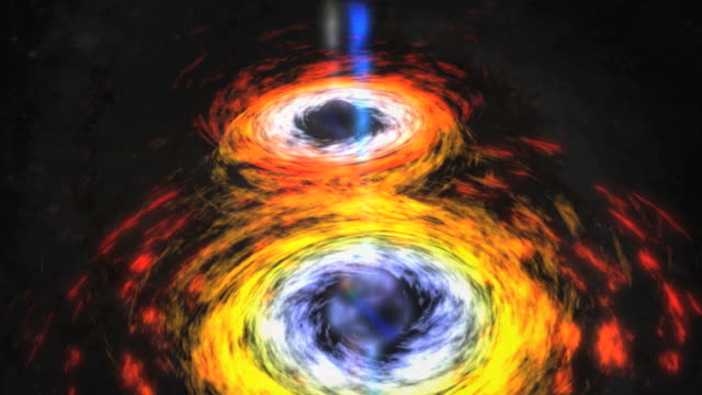 Astrophysics, black holes. Animation of a pair of black holes locked in a death spiral in the centre of a spiral galaxy. When they merge, a massive amount of energy is released in the form of jets. .   Credit NASA.