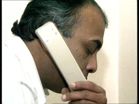 london: walthamstow cms side sri lankan political refugee dayapala thiranagama sitting at desk answers telephone cms side thiranagama on telephone... - voice stock videos & royalty-free footage