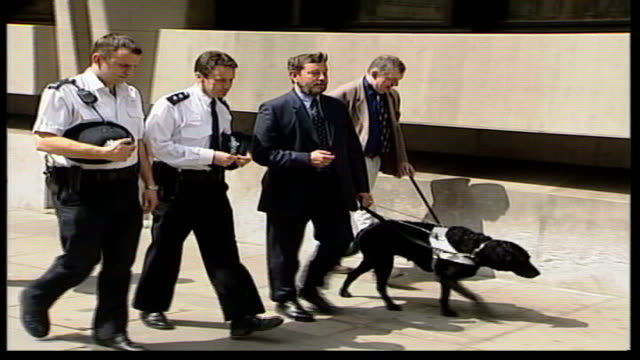 LMS David Blunkett MP along street with police officers guide dog GVs Asylum seekers in dining room of reception centre