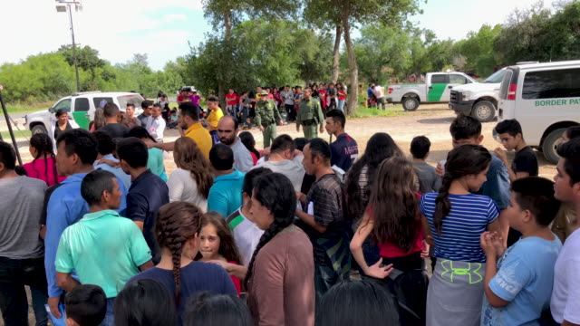 asylum seekers wait in line to be interviewed by u.s. border patrol after being taken into custody on july 02, 2019 in los ebanos, texas. hundreds of... - mcallen texas stock videos & royalty-free footage