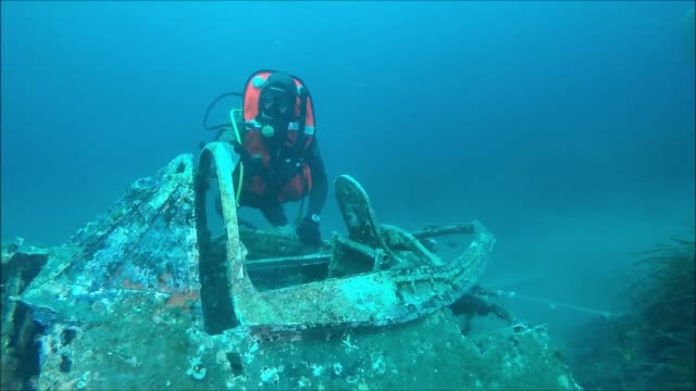 at 18 meters deep off the coast of corsica divers of the french navy supervised by a team of american archaeologists seek the remains of a pilot of a... - archaeologist stock videos & royalty-free footage