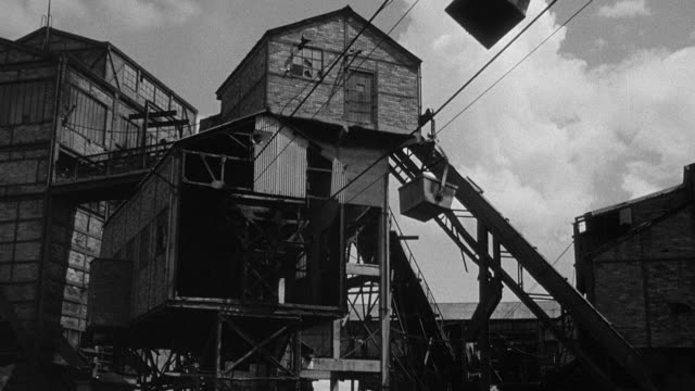 MONTAGE At a colliery, dirt is carried in a bucket traveling on an aerial ropeway over a pit as a worker catches the bucket at the other end / Wales, United Kingdom