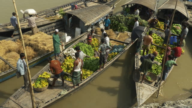 vidéos et rushes de at a colourful monthly market families and traders converge by boat to barter sell and engage local produce and supplies in rural bangladesh - foin