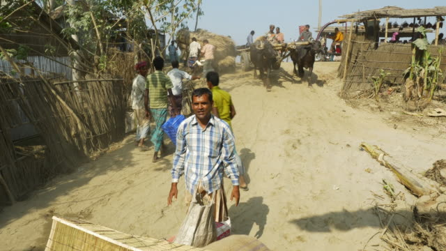 At a colourful monthly market families and traders converge by boat to barter sell and engage local produce and supplies in rural Bangladesh