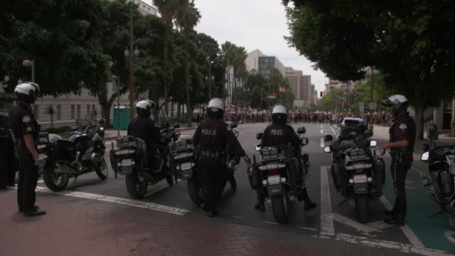 at a good distance from los angeles city hall a group of 7 motor officers guard a demonstration denouncing george floyd's police killing - focus on foreground stock videos & royalty-free footage