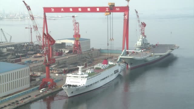 at a northern quayside chinas first aircraft carrier dwarfs nearby vessels its take off ramp rising higher than the top deck of the cruise ship at... - navy stock videos & royalty-free footage