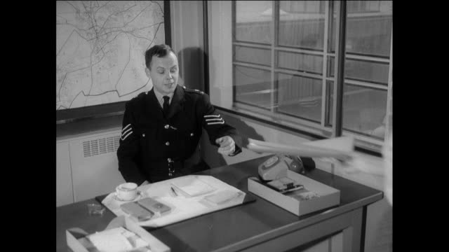montage at a police station, a clerk bringing a file to a police officer who is mapping a location on a board behind his desk / chester, england, united kingdom - file clerk stock videos & royalty-free footage