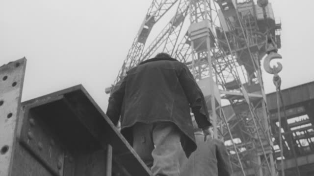 1965 MONTAGE At a power plant under construction, workers walking across the top of a steel beam and welding, with crane working overhead / United Kingdom