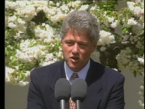 vídeos de stock, filmes e b-roll de at a press conference outdoors at the white house, president bill clinton stands behind a lectern with two microphones on top of it, and says these... - autoimolação
