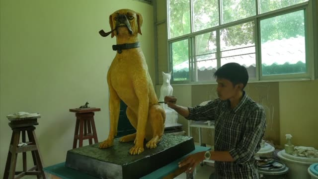 At a studio near Bangkok a pair of immaculate metre high statues of the dogs of Thailand's late King Bhumibol Adulyadej are getting a last lick of...