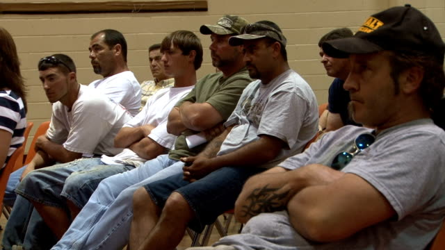 at a town meeting, gulf fishermen sign claim forms for lost income for bp officials. gulf fishermen sign up for bp benefits at town mee on may 14,... - stephenie hollyman stock videos & royalty-free footage