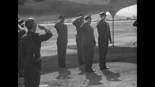 At airfield in Korea Air Force officer pins stars on epaulets of uniform of General Earle Partridge Commander of 5th Air Force promoting him to...