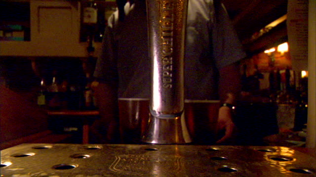 ms body of male bartender behind draught tap picking up two full pint glasses of cold beer sitting them on bar fg iconic bitter pale ale lager... - pilsner stock videos & royalty-free footage