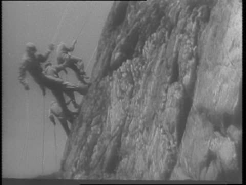 at camp hale colorado / uniformed cliffscalers show climbing and rappelling techniques on western peak in practice for rough road to berlin - anno 1943 video stock e b–roll