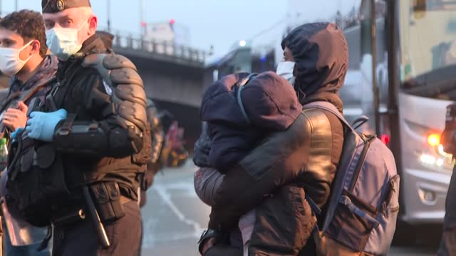 stockvideo's en b-roll-footage met at dawn, at the foot of the stade de france on the outskirts of paris, french police begin clearing a large migrant camp in saint-denis - dawn french