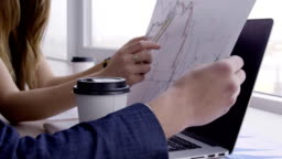 At desk woman with a pen in her hands shows the man a chart on paper