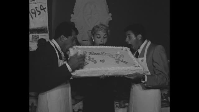 VS At dinner party in 500 Club Dean Martin Jerry Lewis and Janet Leigh hold sheet cake pretending to bite into it / guests at tables / Martin and...