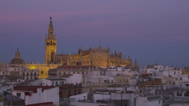 LS HA at dusk over rooftops of historic city center to cathedral (western façade) and La Giralda belltower